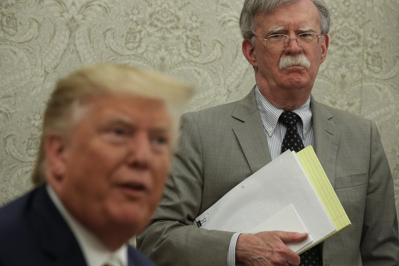 Bolton standing, holding papers, behind Trump, seated, who is speaking to the press