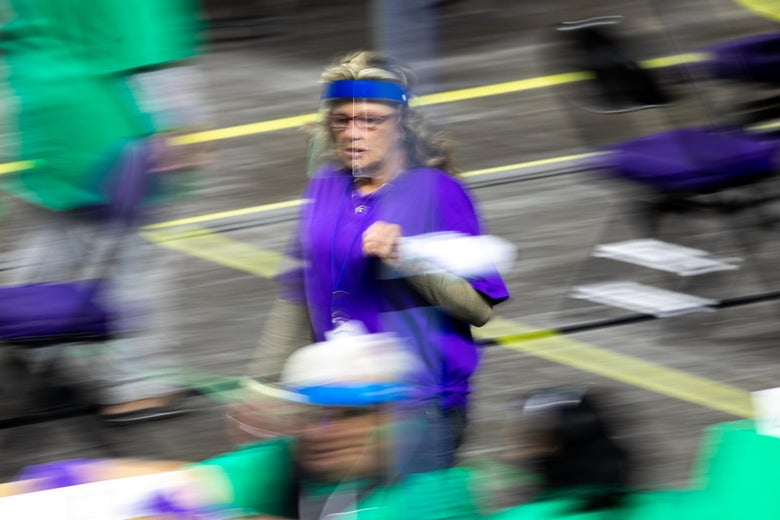 A woman in a purple shirt and a face shield walks through the recount area.