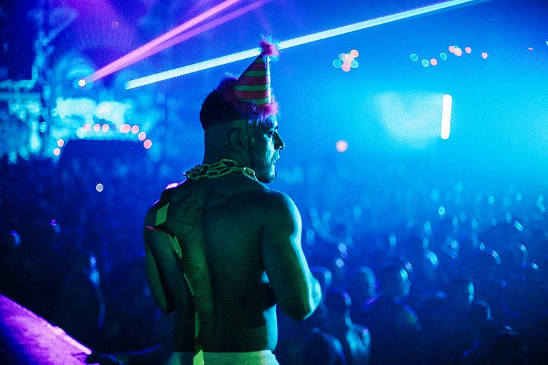 A topless man wearing a party hat and a chain around his neck stands above a crowd of revelers on the dance floor. Laser beams punctuate the dark scene.