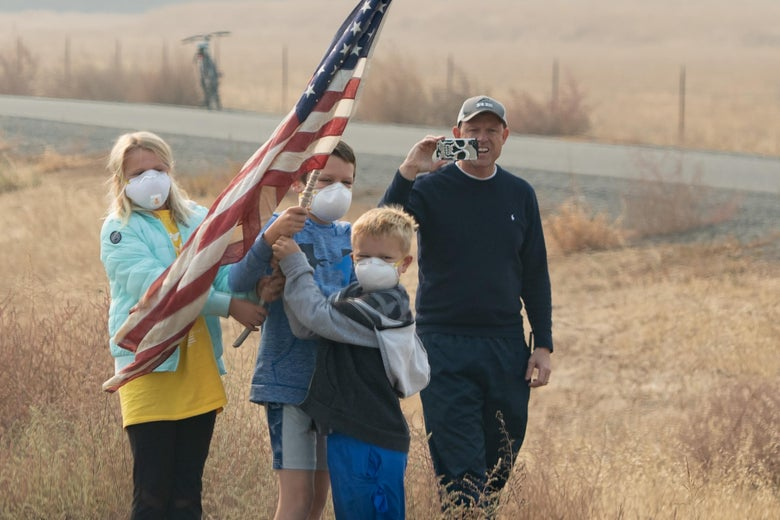 Three children wearing white N95 masks hold up an American flag while a man stands behind them smiling and holding up a phone to take a picture or video.