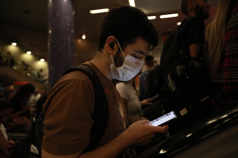 In a crowded airport, a man wearing a mask looks down at his smartphone.