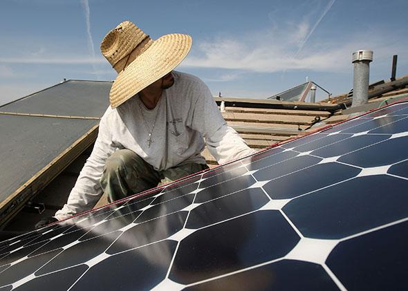 Employees of Solar Forward install solar electric panels on a residential rooftop.