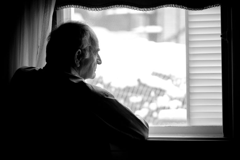 Isolated older man seated and looking out a window.