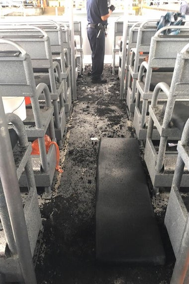 The seats and floor of the boat, with layers of ash and debris
