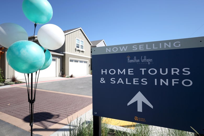 Balloons and a sign advertising new homes for sale in front of a suburban development of single-family homes in Novato, California, in September
