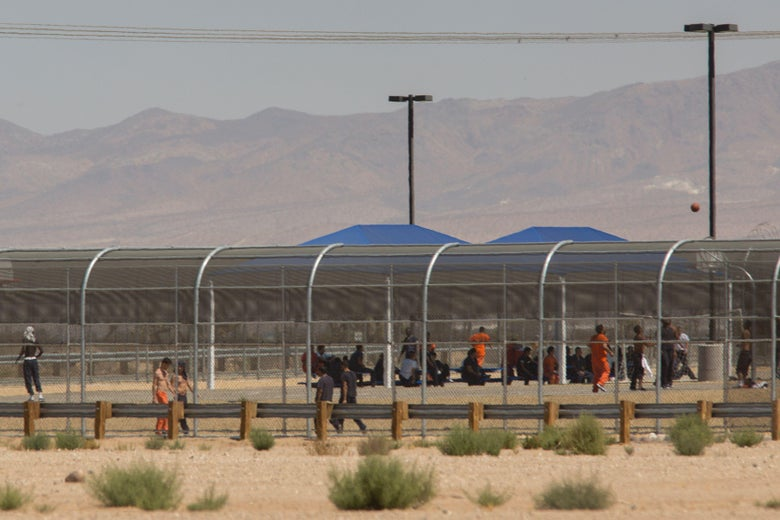 Adults in prisonlike clothes can be seen behind a fenced-off facility in the desert with mountains in the background.