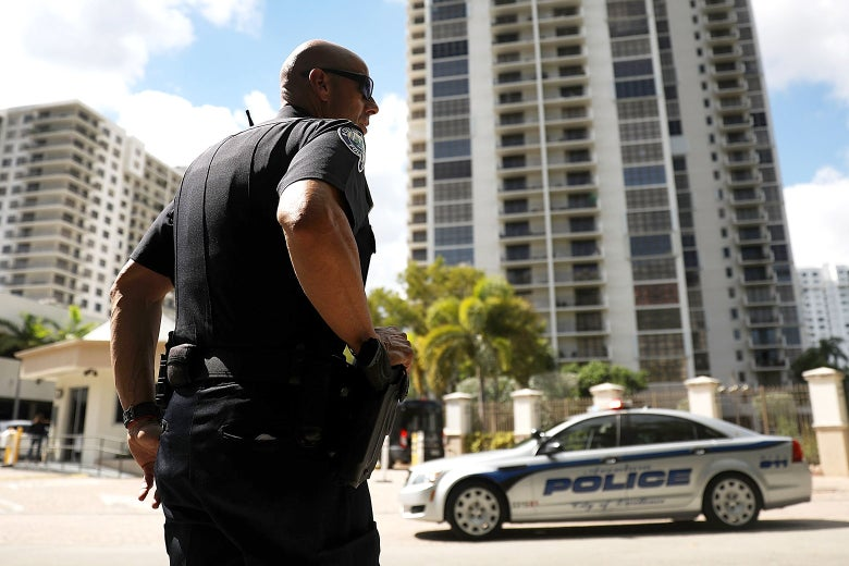 A police officer standing outside a tall building.