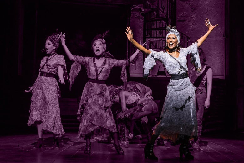 Jewelle Blackman dances and sings with arms outstretched onstage beside the two other Fates