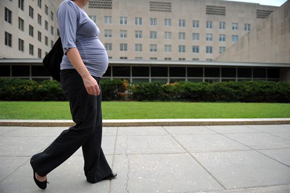 A pregnant woman due in six weeks walks outside the State Department on August 5, 2010 in Washington, DC.