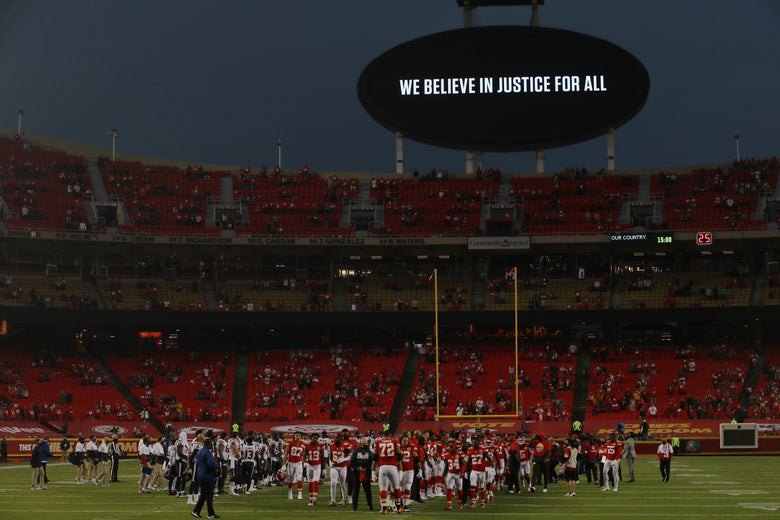 """Players from the Kansas City Chiefs and Houston Texans unite on a football field under a sign that reads """"We Believe in Justice for All."""""""