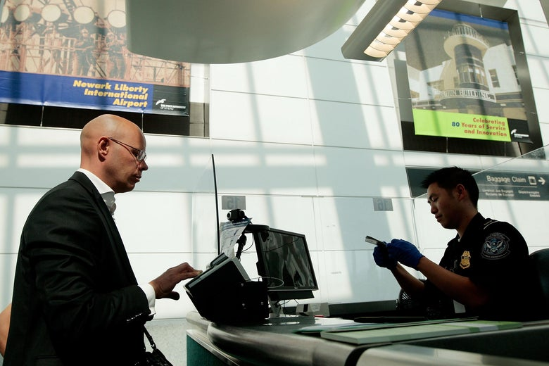 A traveler stands beside a desk as a TSA official examines his passport.