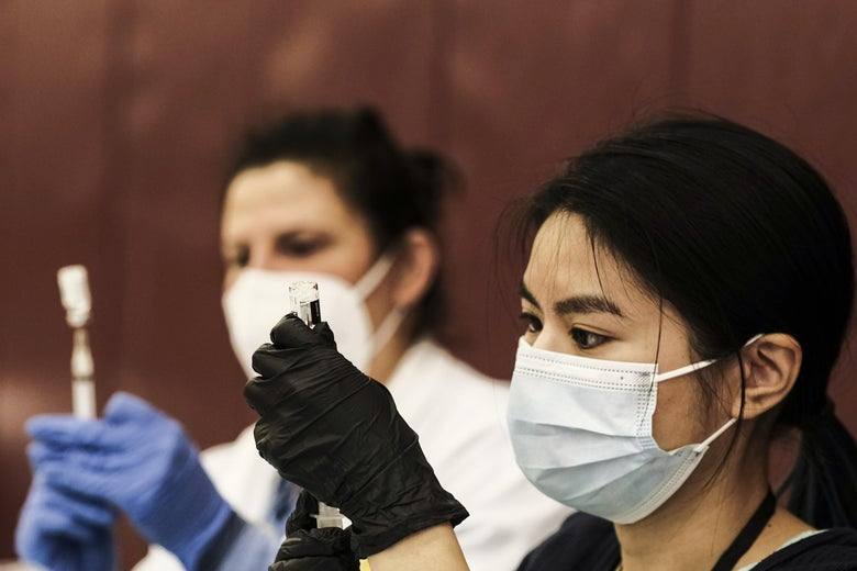 A pharmacist volunteer prepares doses of the Johnson and Johnson COVID-19 vaccine while wearing a mask.