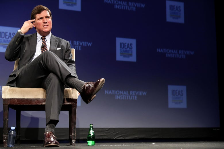 Tucker Carlson points to his head and grimaces while seated onstage at an event.