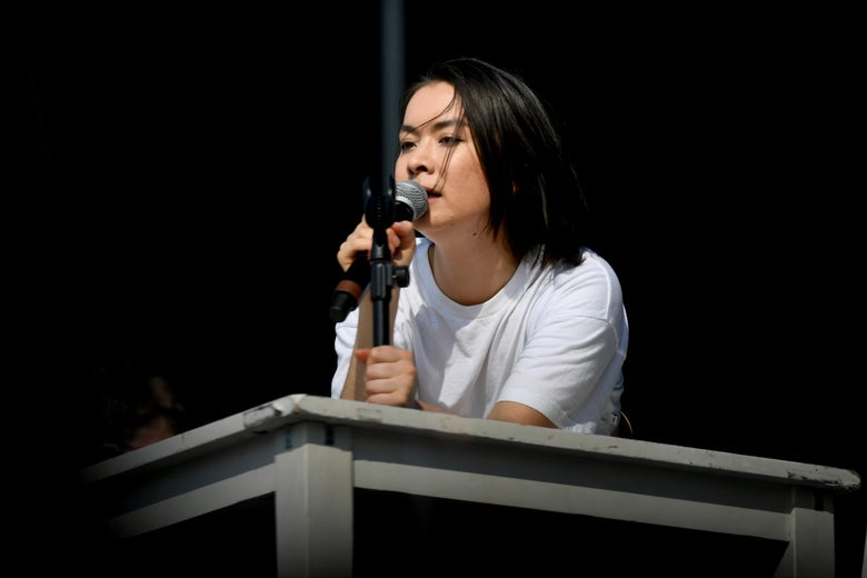 A woman with short black hair wearing a white T-shirt sings into a microphone in her hand. She is leaning on a gray table onstage.