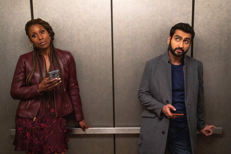 Issa Rae and Kumail Nanjiani stand apart, their phones out, not looking at each other.