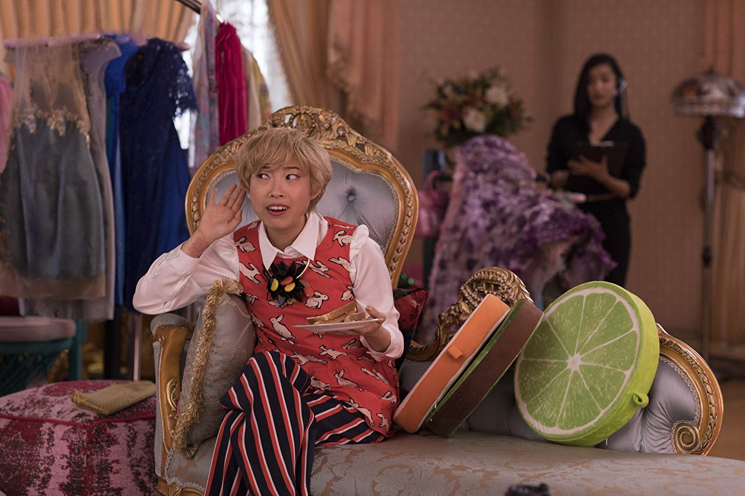 Awkwafina, wearing a short blonde wig, sits on a couch, holding a plate with her hand to her ear