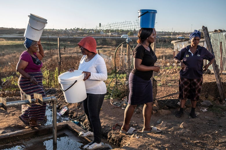 Women with buckets stand in line to get water from a tap.