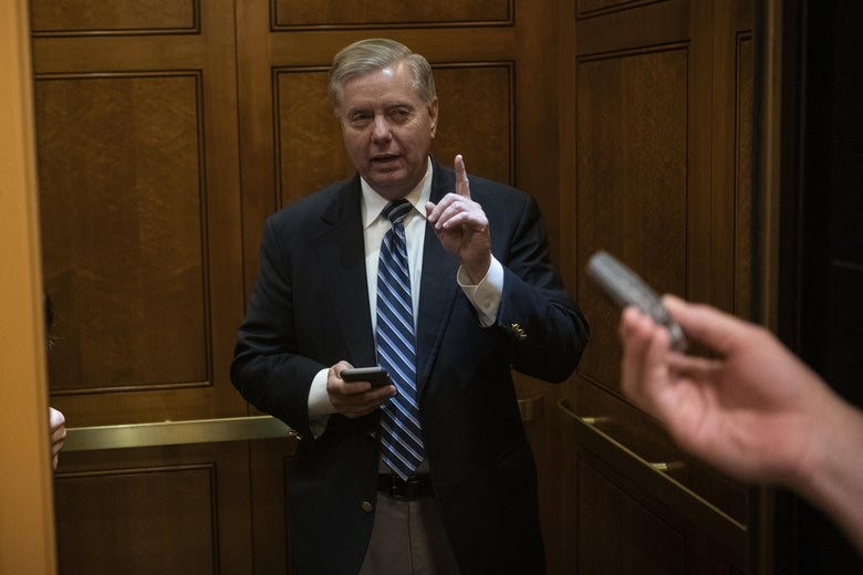 Lindsey Graham speaks to reporters while getting on an elevator.
