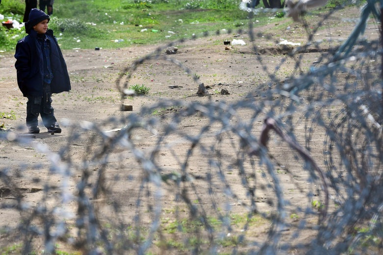 A young migrant boy stands behind a barbed wire fence.