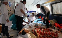 Medics look after an injured man on board a MedEvac boat. Click to expand image.