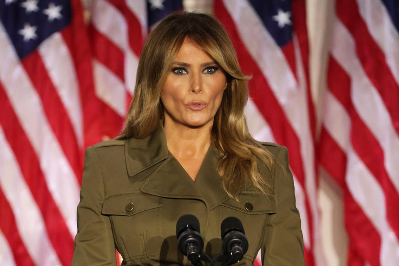 Melania Trump, in an olive-green military-looking jacket, speaks into a cluster of microphones, backed by several U.S. flags.