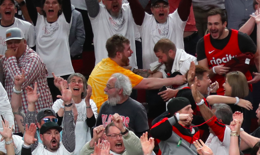 A bearded fan in a yellow shirt embraces a friend with a look of what can only be described as ecstatic spiritual fulfillment.