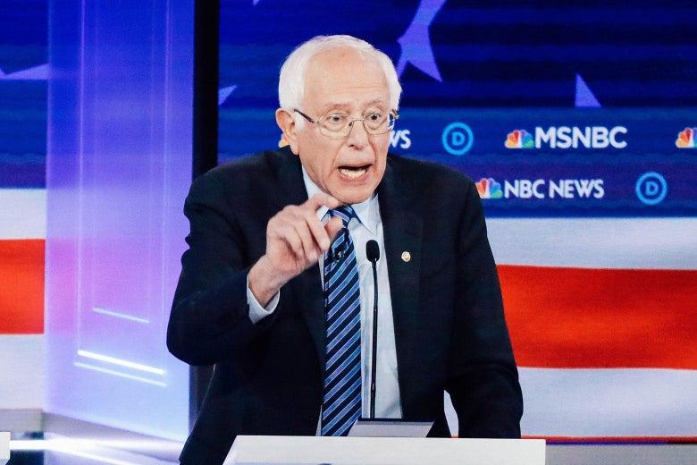 Bernie Sanders gestures while speaking behind a podium at the debate.