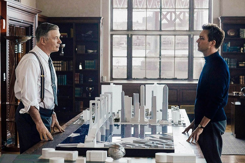 In a still from Motherless Brooklyn, Alec Baldwin and Edward Norton stare each other down, with a model of New York City on a table between them.