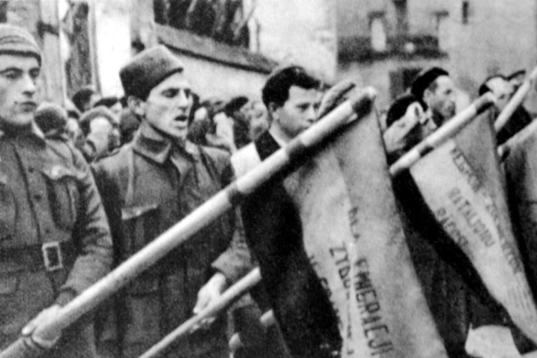 Soldiers are seen in a line carrying flags.