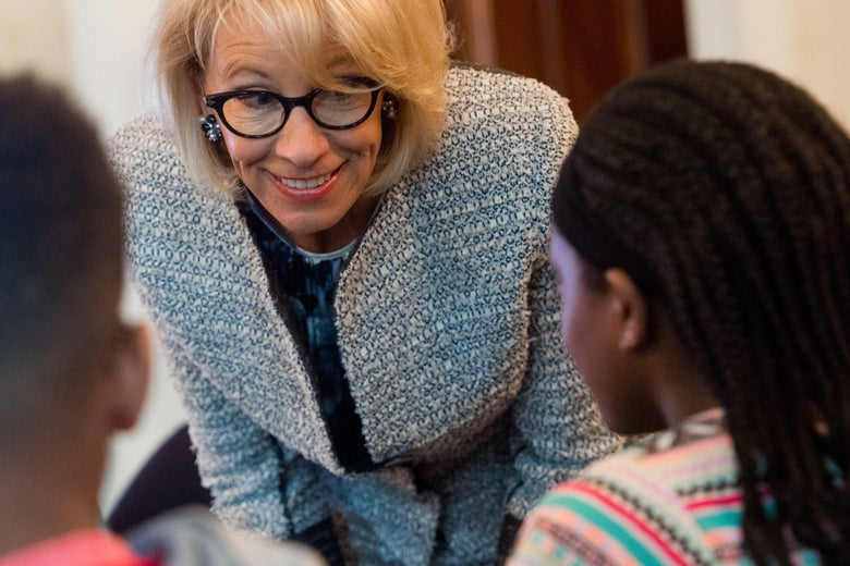 Betsy DeVos bends over and smiles at kids.