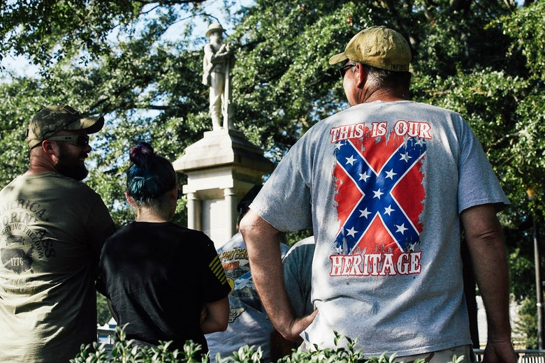 "A man wearing a T-shirt with the words ""This is our heritage"" around the Confederate battle flag stands in front of a Confederate statue among other statue supporters."