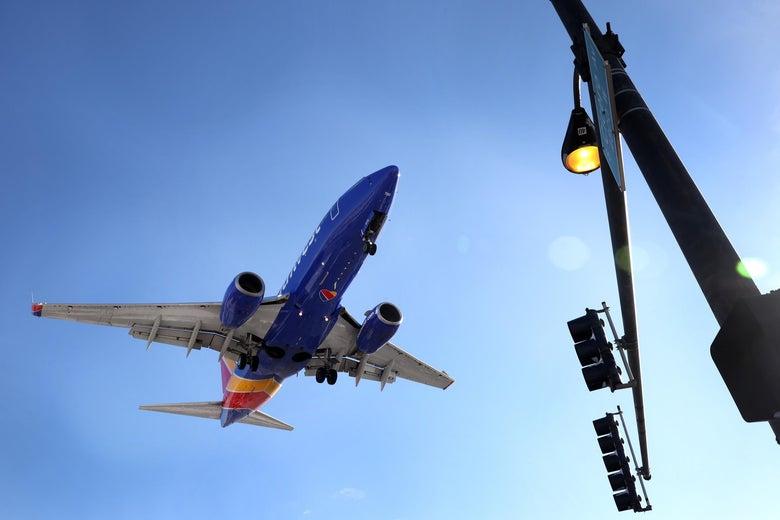 A plane flies above a traffic light.