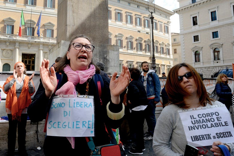 Protesters hold hand-made signs in Italian.