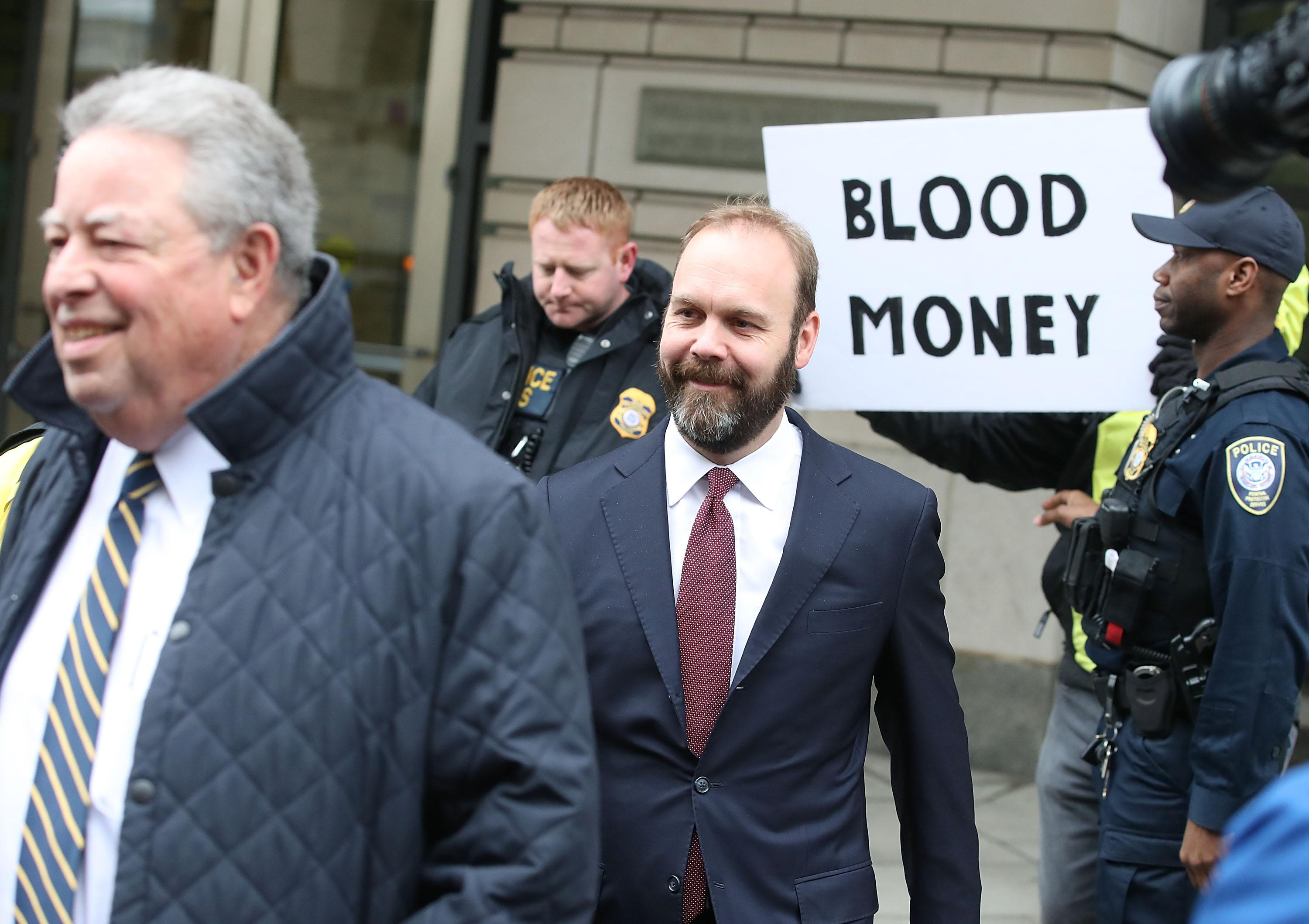 "Rick Gates walks out of the Prettyman Federal Courthouse in front of a prostester holding a sign reading ""Blood Money,"" on Feb. 23, 2018 in Washington, DC."