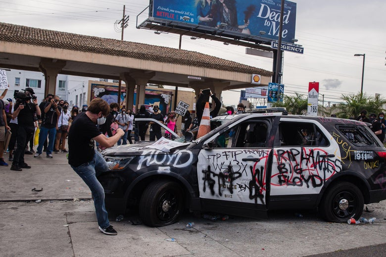 A demonstrator kicks a damaged police vehicle in Los Angeles on May 30, 2020.