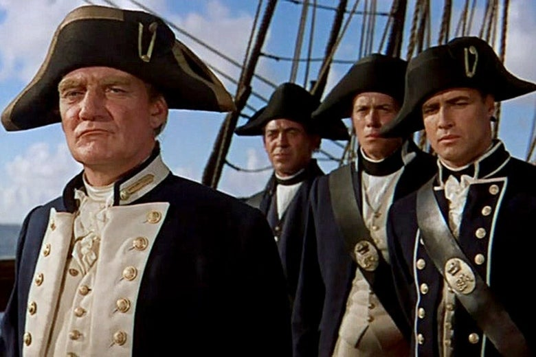 Capt. Bligh stands in the foreground, looking self-satisfied, as a Brando's Fletcher Christian looks on skeptically