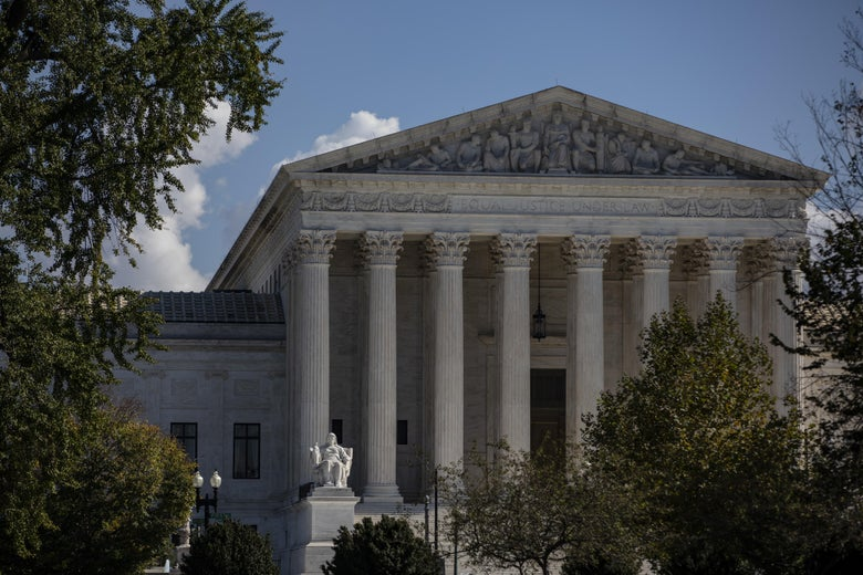 Trees on each side form the foreground of this image of the Supreme Court building with its grand columns.