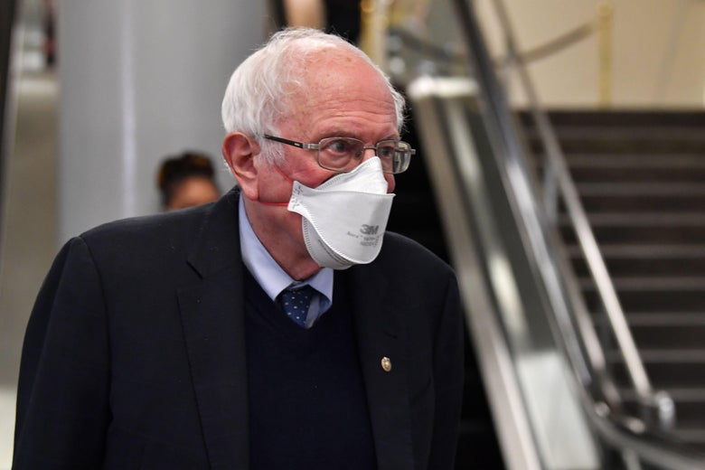 Sanders walks through the halls of Congress with a mask.