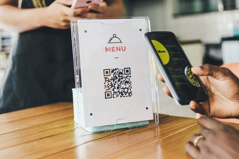 """A QR code on a sheet of paper labeled """"MENU"""" standing upright on a table. Someone holds their phone up to the code to scan it, displaying the menu on the smartphone screen."""