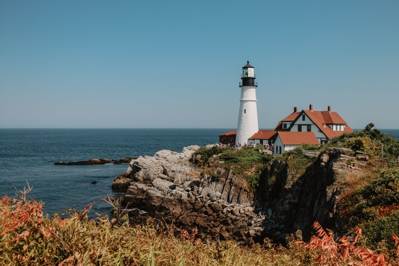 A lighthouse and small house on the edge of a cliff on the ocean in Portland, Maine.