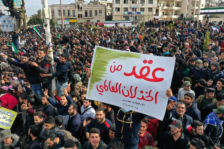 """Syrians carrying a placard that reads """"A decade of international letdown"""""""