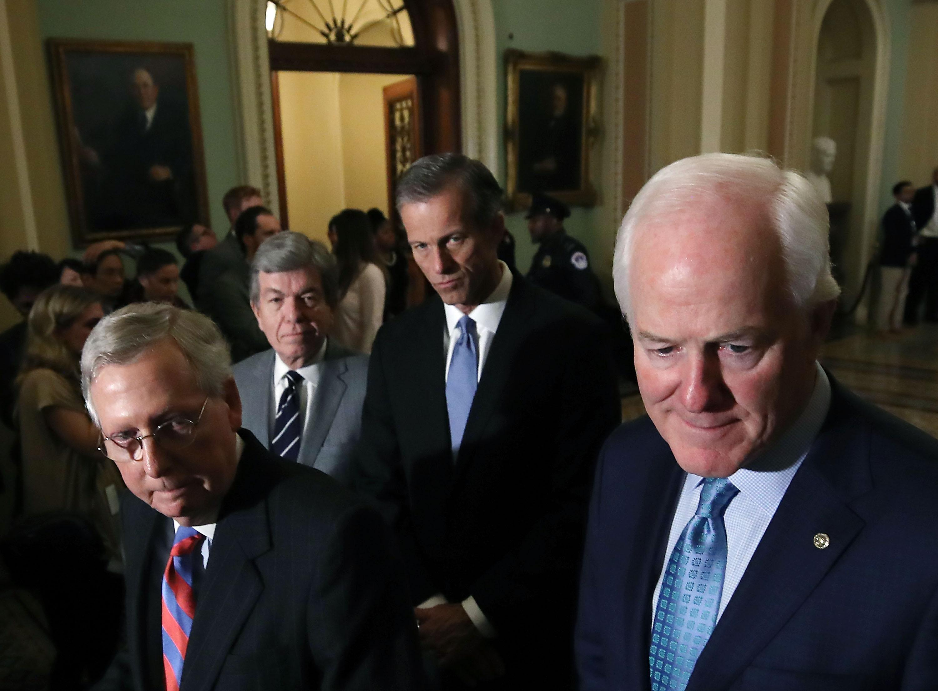 WASHINGTON, DC - DECEMBER 05: (L-R) Senate Majority Leader Mitch McConnell (R-KY), Sen. Roy Blunt (R-MO), Sen. John Thune (R-SD), and Sen. John Cornyn (R-TX) listen to reporters questions about the tax reform bill the Senate passed last week, at US Capitol on december 5, 2017 in Washington, DC.  (Photo by Mark Wilson/Getty Images)
