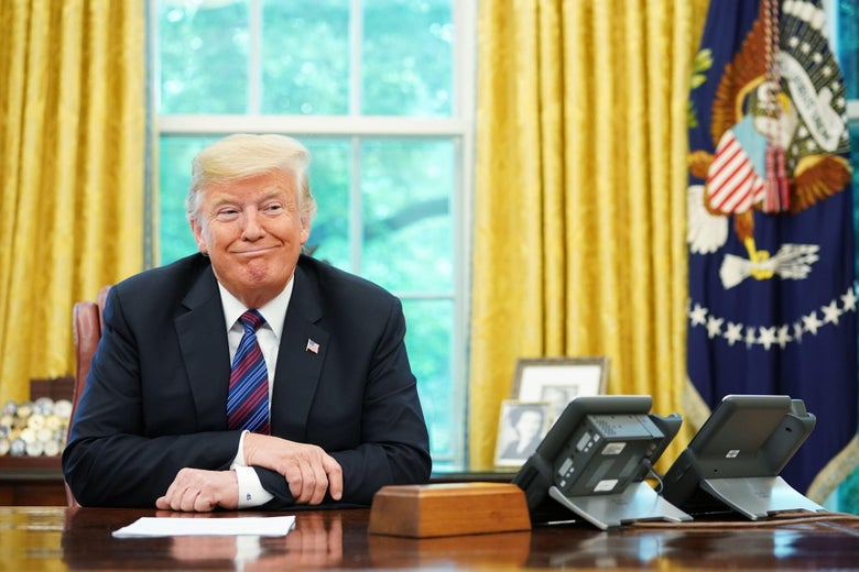President Trump arms crossed and smirking at his desk in the Oval Office during a phone conversation.