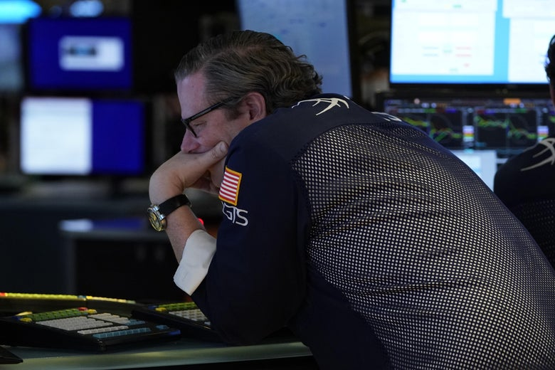A trader hunches over a keyboard with his hand over his mouth