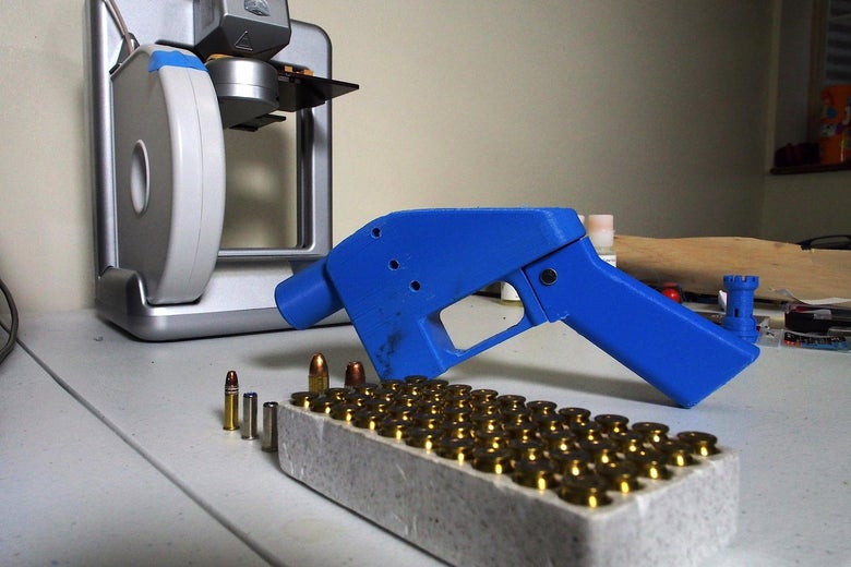 A blue Liberator pistol on a table next to a box of bullets and the 3-D printer on which its components were made.