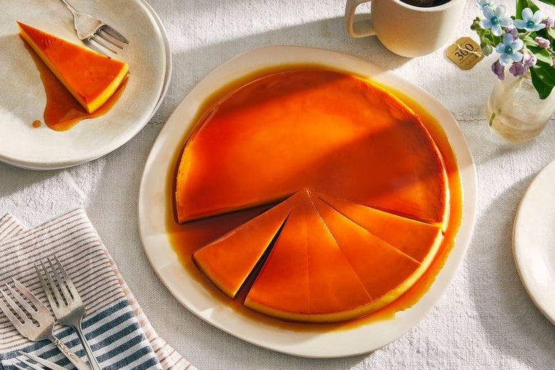 Orange flan cut into slices with dessert forks nearby.