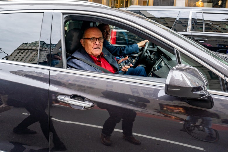 Giuliani holds his phone, sitting in the passenger seat of a black car