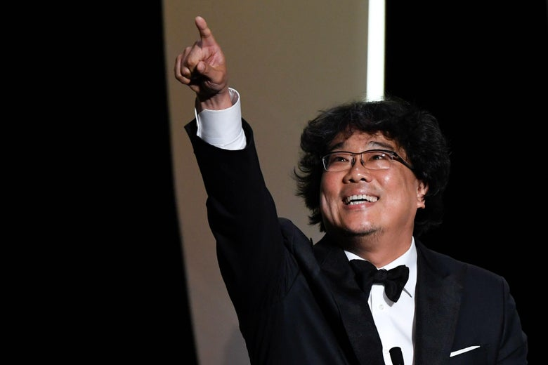 Director Bong Joon-ho smiles and raises his hand in triumph.