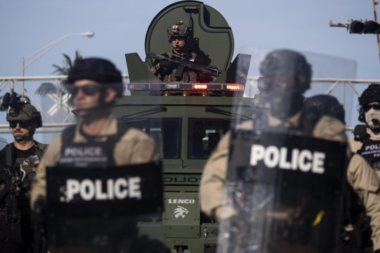 Police in riot gear stand in front of an armored vehicle