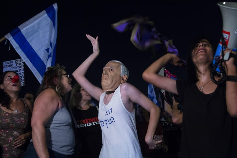 A young woman, wearing a rubber mask of Benjamin Netanyahu over her head, dances in a crowd of people.
